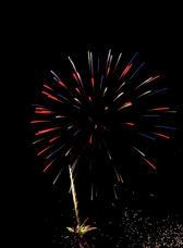 a colourful rocket lights up the night sky on bonfire night