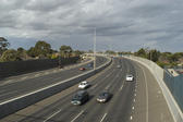 Cars travelling towards the camera on a multi lane highway which curves away to the left under a cloudy sky