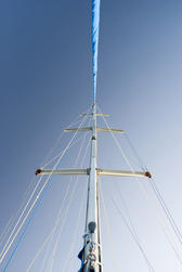 Metal mast of a small pleasure sailing yacht with its rigging against a clear blue sky