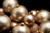 Pile of different luxurious golden Christmas balls with patterns and textures against a dark background with copyspace