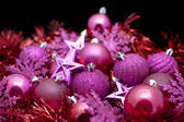 Festive party background of assorted pink Christmas decorations in a random pile for your seasonal greetings