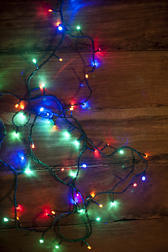 Sparkling garland of colorful Christmas lights lying entwined on a wooden table in a seasonal background, overhead view