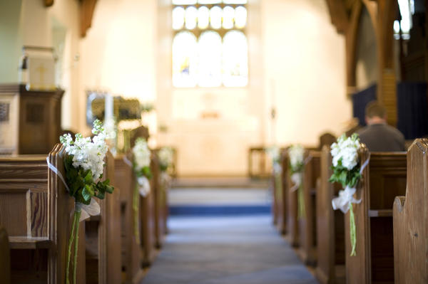 a narrow depth of field image of a church aisle decorated with white english stocks flowers