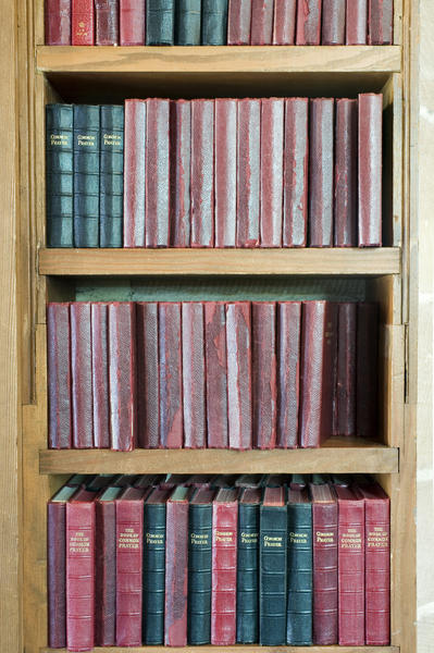 rows of hymn and prayer books on a church bookshelf
