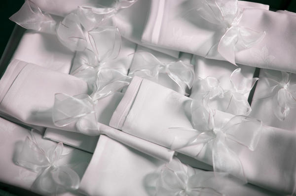 a pile of white linen napkins decorated with white lace ribbon for a wedding