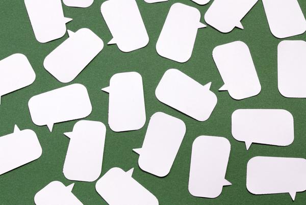 paper speech bubbles laid on a green background, concept of open discussion and debate