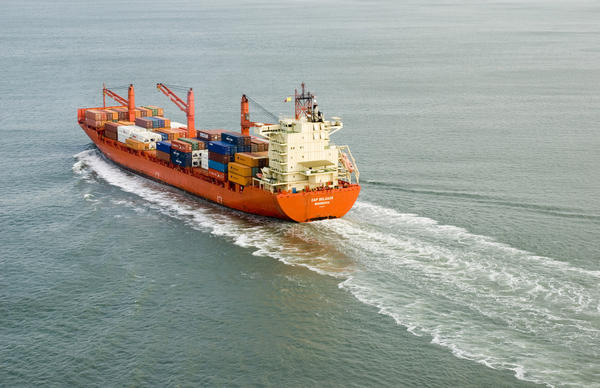 A large container ship laden with containers leaves a wide wake as it heads in to port