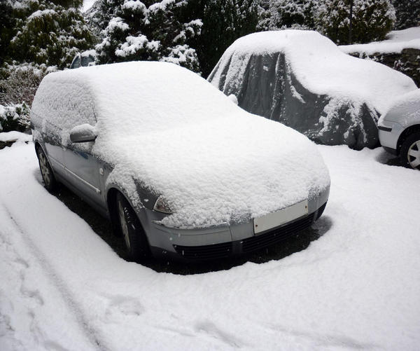 a car covered in a layer of fresh snow