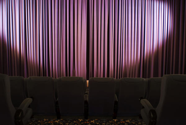 Purple theatre curtains with empty audience seating in the foreground