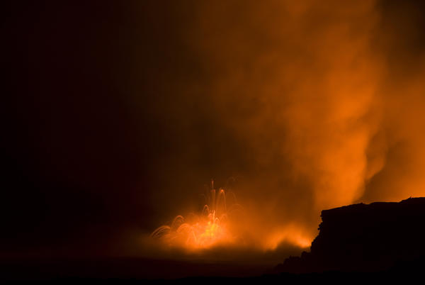 long exposure photo of view of lava entering the ocean spewing clouds of steam, near Kalapana, Hawaiis Big Island