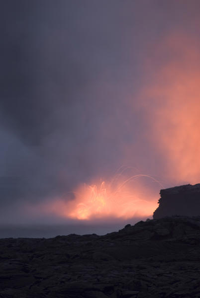 red glowing lava entering the ocean and spewing clouds of steam into the air, near Kalapana, Hawaiis Big Island