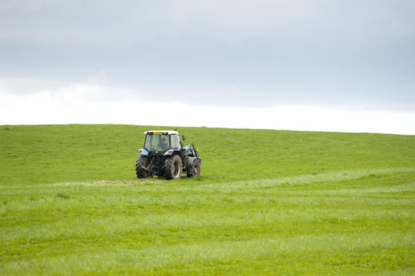 stock image Farmer working with his tractor on a lush green pasture in the English countryside to ensure the best possible grazing for his livestock