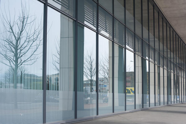 Modern building foyer with a glass walled front giving a view onto an urban forecourt and with a large empty internal space