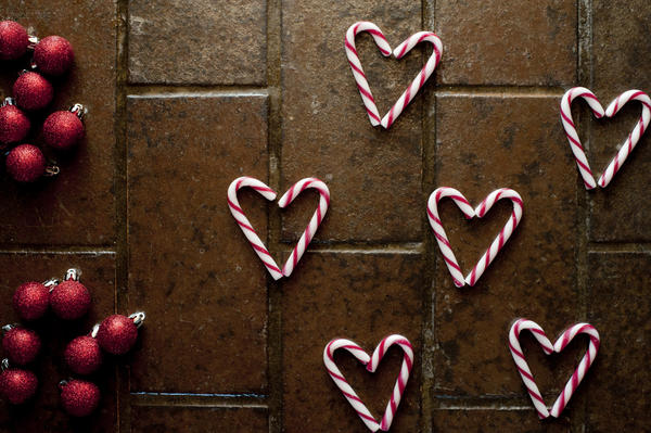Christmas candy background pattern with red and white striped candy canes arranged as heart shapes on brown tiles with red Christmas baubles, overhead view
