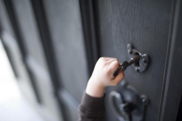 Child Reaching Up To Unlock An Old Wooden Door 7250