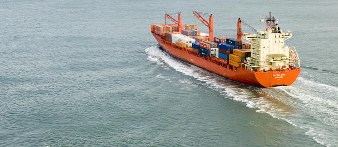 stock image A large cargo ship full of shipping containers sailing into port