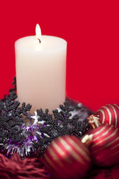 christmas candle, baubles, decorations and tinsel garland on a red background
