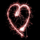 a glowing red sparkling love heart shape on a black background