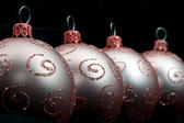 Oblique row of gold Christmas balls decorated with glitter curlicues for a dramatic seasonal background