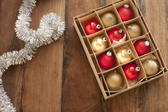 Christmas ornaments background with colorful gold and red baubles in a box alongside a silver tinsel border with copyspace for your greeting on a wooden background, overhead view