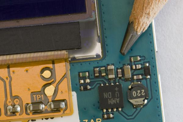 macro image of the tiny electronic component inside a mobile phone compared to the tip of a pencil for scale