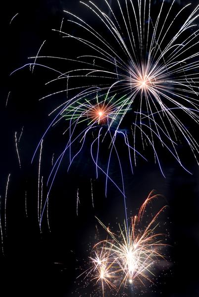 A long exposure image tracing shapes as fireworks explode during a fireworks display