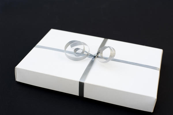 a white gift box bound with a silver coloured ribbon