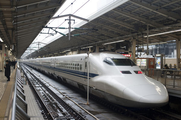 Shinkansen bullet train, or high speed tain, pulled up at a platform in a Japanese railway station