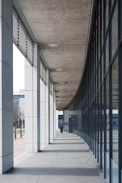 External covered passageway on a modern commercial building with a curved receding perspective in an urban environment