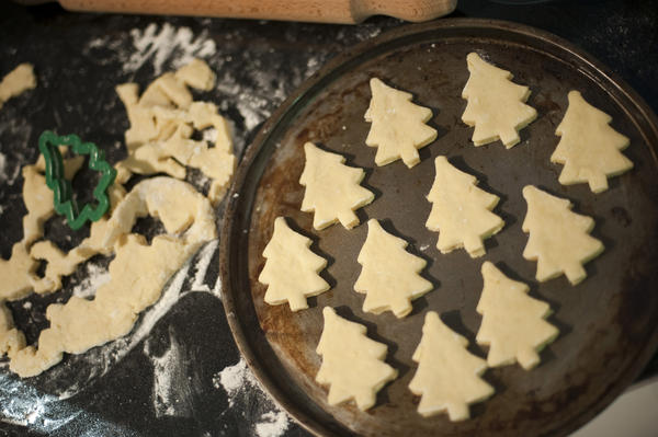 High angle view of cookies or biscuits in the shape of traditional Christmas trees arranged on a baking tray for cooking during Xmas baking