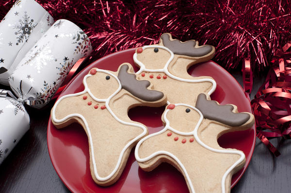 Reindeer Christmas biscuits with chocolate antlers, red noses and collars served on a festive table with crackers and decorations