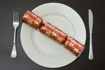 a modern christmas dinner table place setting with a cracker on a plate