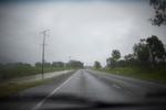 driving down an empty country road on a wet day