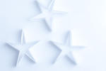 Delicate fragile paper stars on a white background for an ethereal spiritual Christmas background