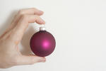 Man holding a colorful purple Christmas bauble in his fingers displaying it to the camera over a white background with copyspace for your holiday greeting
