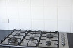 Clean modern gas stove with five burners in a black kitchen counter with white splash back